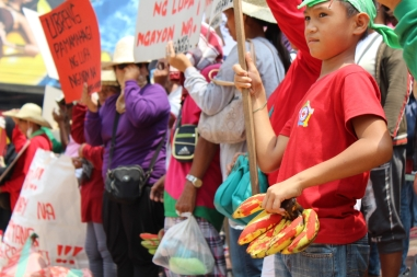 This child of a worker holds up a protest sign while, in his other hand, he holds bananas smeared with red paint to symbolize the violent tactics used by the plantation owners to prevent agrarian reform beneficiaries from reclaiming their lands.