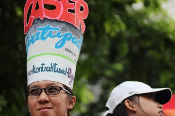 A labor rights advocate wears a hat with the letters CASER, which stands for Comprehensive Agreement on Socio-Economic Reforms, a main agenda of the peace negotiations between the Philippine government and the National Democratic Front of the Philippines (NDFP). The CASER includes provisions that ensure workers' rights such as job security, just wages and benefits and an end to contractualization.