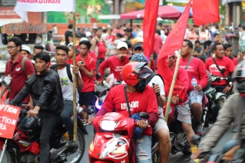 Motorcycle riders, many of them working as couriers and messengers for businesses, join the march as marshalls.